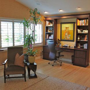 Foto på ett tropiskt arbetsrum, med orange väggar, mellanmörkt trägolv och ett inbyggt skrivbord