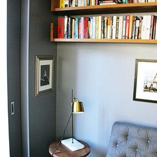 ニューヨークの小さいモダンスタイルのおしゃれなホームオフィス・仕事部屋 (ライブラリー、青い壁、濃色無垢フローリング、造り付け机、黒い床) の写真