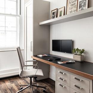 Inspiration för moderna hemmabibliotek, med vita väggar, mörkt trägolv och ett inbyggt skrivbord