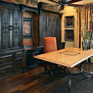 Immagine di un grande ufficio mediterraneo con pareti gialle, parquet scuro, scrivania autoportante, nessun camino e pavimento marrone