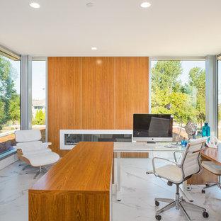 バンクーバーの広いモダンスタイルのおしゃれなホームオフィス・書斎 (白い壁、磁器タイルの床、横長型暖炉、木材の暖炉まわり、自立型机、白い床) の写真