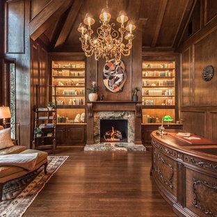 Großes Klassisches Lesezimmer mit brauner Wandfarbe, dunklem Holzboden, Kamin, Kaminumrandung aus Stein und freistehendem Schreibtisch in Los Angeles
