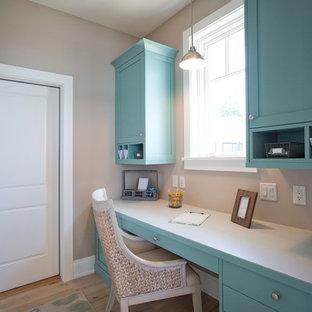 グランドラピッズの広いビーチスタイルのおしゃれなホームオフィス・書斎 (造り付け机、ベージュの壁、淡色無垢フローリング、ベージュの床) の写真