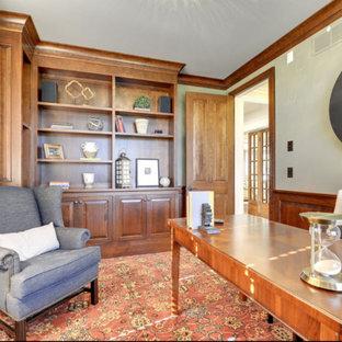 ミネアポリスの中くらいのトラディショナルスタイルのおしゃれなホームオフィス・書斎 (ライブラリー、グレーの壁、カーペット敷き、暖炉なし、自立型机、オレンジの床) の写真