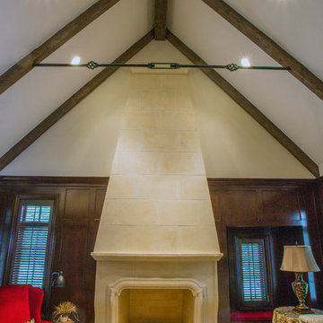 Two Story Limestone Fireplace with Stained Cherry Paneling and Beams
