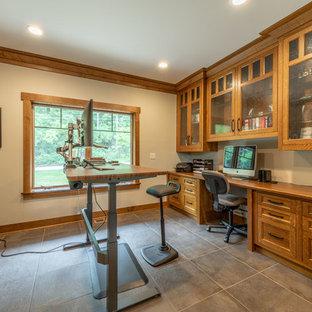 Idee per uno studio american style di medie dimensioni con libreria, pareti beige, pavimento con piastrelle in ceramica, scrivania incassata e pavimento nero