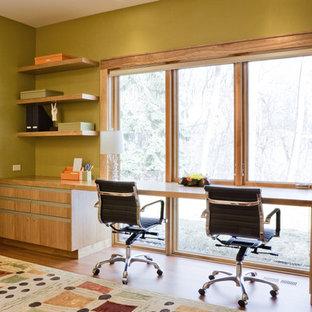 ミネアポリスのコンテンポラリースタイルのおしゃれなホームオフィス・書斎 (緑の壁、無垢フローリング、造り付け机) の写真