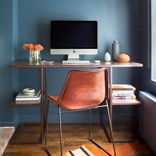 ニューヨークの小さいトランジショナルスタイルのおしゃれな書斎 (青い壁、無垢フローリング、自立型机、暖炉なし、茶色い床) の写真