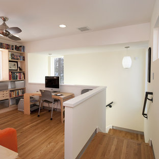 Example of a trendy freestanding desk medium tone wood floor home office design in Austin with white walls