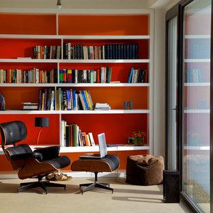 Idee per uno studio minimal con libreria, pareti arancioni e pavimento beige