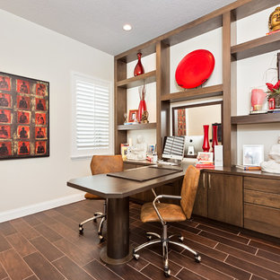 Inspiration for a large built-in desk dark wood floor and brown floor home office remodel in Orlando with white walls and no fireplace