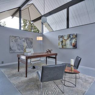 Immagine di un ufficio minimalista di medie dimensioni con pareti marroni, pavimento in cemento, nessun camino, scrivania autoportante e pavimento grigio
