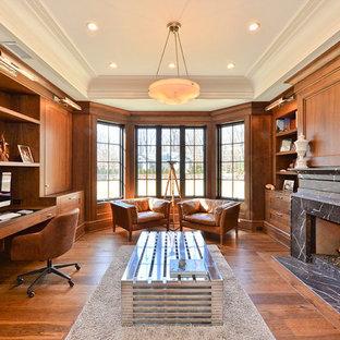ニューヨークの大きいトラディショナルスタイルのおしゃれな書斎 (茶色い壁、無垢フローリング、標準型暖炉、石材の暖炉まわり、造り付け机、茶色い床) の写真