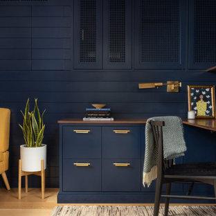 Kleines Klassisches Arbeitszimmer mit Arbeitsplatz, blauer Wandfarbe, hellem Holzboden, Einbau-Schreibtisch, braunem Boden und Holzdielenwänden in New York