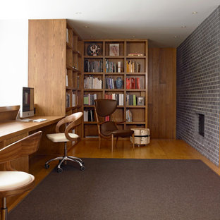 Example of a mid-sized trendy built-in desk medium tone wood floor study room design in New York with white walls, a standard fireplace and a brick fireplace