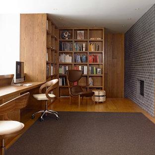 Imagen de despacho actual, de tamaño medio, con suelo de madera en tonos medios, escritorio empotrado, paredes blancas, chimenea tradicional y marco de chimenea de ladrillo