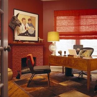 Immagine di un ufficio contemporaneo di medie dimensioni con pareti rosse, parquet chiaro, camino ad angolo, cornice del camino in mattoni e scrivania autoportante
