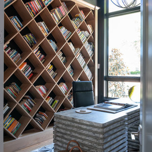 ダラスのコンテンポラリースタイルのおしゃれなホームオフィス・書斎 (黒い壁、無垢フローリング、自立型机、茶色い床) の写真