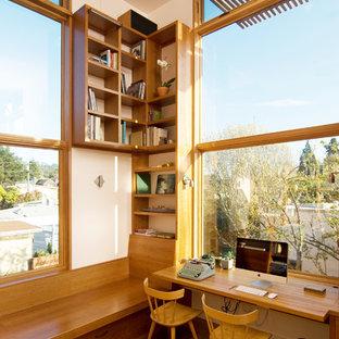 Foto de despacho actual, de tamaño medio, sin chimenea, con paredes blancas, suelo de madera en tonos medios y escritorio empotrado