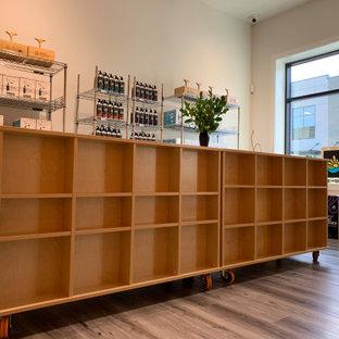 バンクーバーの中サイズのトラディショナルスタイルのおしゃれなアトリエ・スタジオ (茶色い壁、合板フローリング、薪ストーブ、木材の暖炉まわり、造り付け机、白い床) の写真