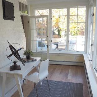 Großes Klassisches Arbeitszimmer mit Arbeitsplatz, gelber Wandfarbe, braunem Holzboden und freistehendem Schreibtisch in Boston