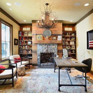 ナッシュビルの中サイズのラスティックスタイルのおしゃれなアトリエ・スタジオ (無垢フローリング、標準型暖炉、石材の暖炉まわり、自立型机、ベージュの壁、茶色い床) の写真