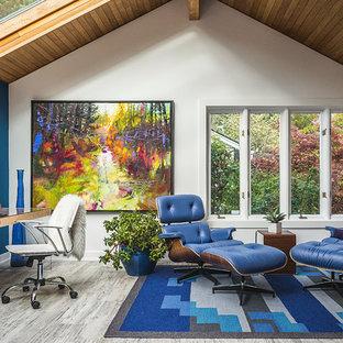 Inredning av ett modernt hemmabibliotek, med blå väggar, ett fristående skrivbord, klinkergolv i porslin och grått golv