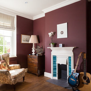 This is an example of a medium sized traditional home studio in Other with medium hardwood flooring, a standard fireplace and purple walls.