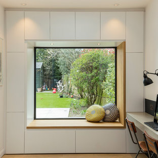 Medium sized contemporary study in London with white walls, no fireplace and a built-in desk.