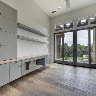 Exempel på ett stort modernt arbetsrum, med vita väggar, ljust trägolv, ett inbyggt skrivbord och beiget golv