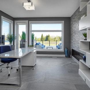 Modern inredning av ett stort hemmabibliotek, med grå väggar, klinkergolv i keramik, en dubbelsidig öppen spis, en spiselkrans i trä, ett fristående skrivbord och grått golv