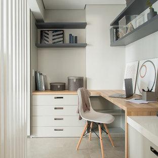 Diseño de despacho actual con paredes grises, suelo de cemento, escritorio empotrado y suelo gris