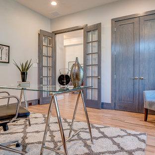 Ejemplo de despacho clásico renovado, sin chimenea, con paredes grises, suelo de madera clara y escritorio independiente