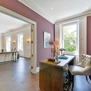 Immagine di un ufficio con pareti viola, pavimento in legno massello medio e scrivania autoportante