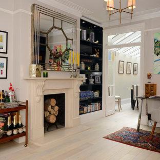 Imagen de despacho tradicional con paredes blancas, suelo de madera clara, chimenea tradicional, marco de chimenea de yeso, escritorio independiente y suelo beige