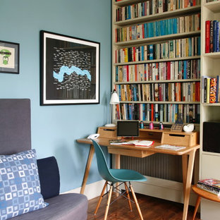 Photo of an eclectic study in London with blue walls, medium hardwood flooring and a freestanding desk.