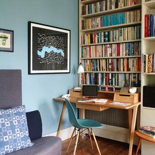 Eklektisches Arbeitszimmer mit blauer Wandfarbe, braunem Holzboden, freistehendem Schreibtisch und Arbeitsplatz in London
