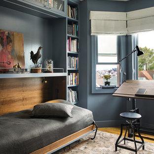 Modelo de despacho clásico renovado con paredes azules, suelo de madera en tonos medios y escritorio independiente