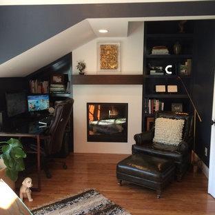 Immagine di un ufficio tradizionale di medie dimensioni con pareti nere, pavimento in legno massello medio, camino classico, cornice del camino in intonaco e scrivania autoportante