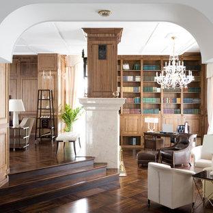 Idee per uno studio eclettico di medie dimensioni con libreria, pareti marroni, pavimento in legno massello medio, camino bifacciale, cornice del camino in pietra, scrivania autoportante e pavimento marrone