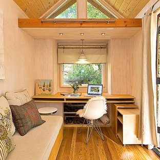Идея дизайна: маленькое рабочее место в современном стиле с паркетным полом среднего тона, бежевыми стенами и встроенным рабочим столом без камина