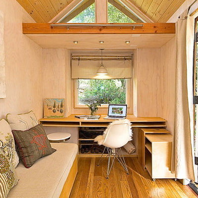 Small trendy built-in desk medium tone wood floor study room photo in Los Angeles with beige walls and no fireplace
