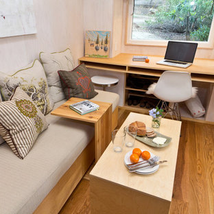 Example of a small trendy built-in desk medium tone wood floor study room design in Los Angeles with beige walls and no fireplace