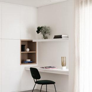 Foto på ett stort funkis arbetsrum, med betonggolv, grått golv, vita väggar och ett inbyggt skrivbord