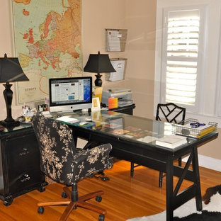 Home office - contemporary freestanding desk medium tone wood floor home office idea in Sacramento with beige walls