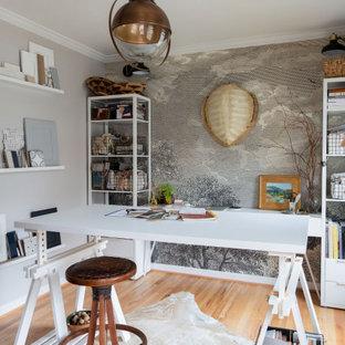 Cette image montre un bureau bohème de taille moyenne et de type studio avec un mur gris, un sol en bois clair, aucune cheminée, un bureau indépendant, du papier peint et un sol beige.