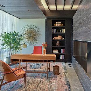 Foto di un grande studio contemporaneo con scrivania autoportante, pavimento grigio, pareti rosse e pavimento in cemento