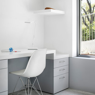 Inspiration for a mid-sized 1960s built-in desk concrete floor and gray floor study room remodel in Austin with white walls