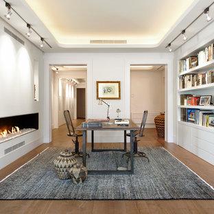 Идея дизайна: рабочее место среднего размера в стиле лофт с белыми стенами, темным паркетным полом, горизонтальным камином, фасадом камина из штукатурки и отдельно стоящим рабочим столом