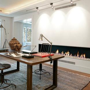 バルセロナの中サイズのインダストリアルスタイルのおしゃれな書斎 (白い壁、濃色無垢フローリング、横長型暖炉、漆喰の暖炉まわり、自立型机) の写真